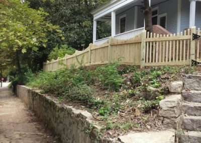 picket fence view from sidewalk with stone retaining wall atlanta